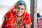 Portrait of an ethnic Rajasthani women wearing beautiful bright colourful clothes, waiting at a bus stop in Rajasthan