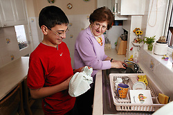 Grandmother washing dishes in the kitchen with her grandson helping,