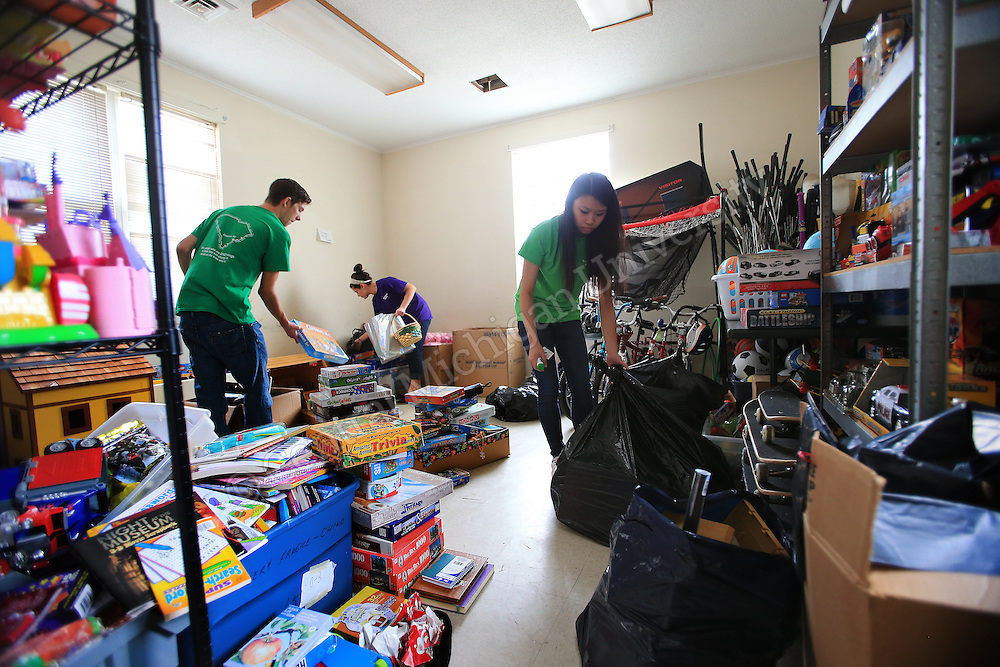 From left: , Tod Carnish, of Mentor, OH, Katherine Jabboury, of Troy, and Amy Yu, of Grand Blanc, work together to sort sports and game donations in an area of the house. They were among eleven CMU students volunteering during her Alternative Break at the Carolina Youth Development Center in North Charleston, SC, spending the week to help with projects to improve the center and in the community.  CMU is ranked fourth in the nation for the number of students participating in Alternative Breaks and fifth in the country for the most trips coordinated by a university. The program organizes about 40 trips each year with more than 400 students participating. Photo by Steve Jessmore/Central Michigan University