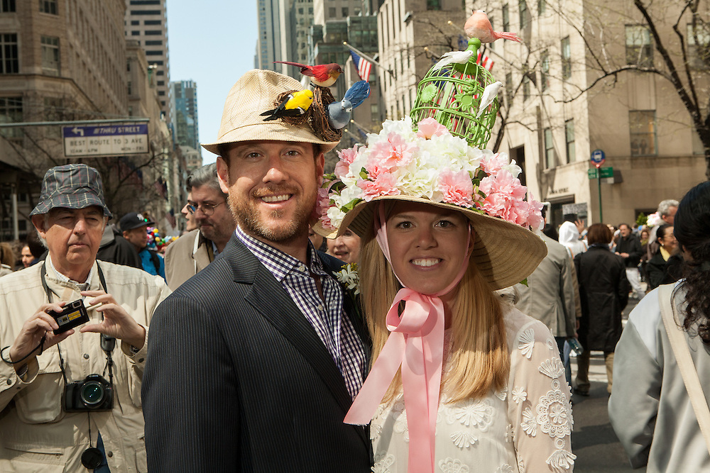 A couple sporting hats featuring birds, his wild, hers caged.