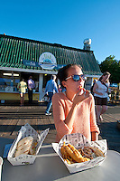 Taylor enjoys some fish and chips from The Fish Store on the dock at Fisherman's Wharf on a summer's evening in Victoria, BC, Canada