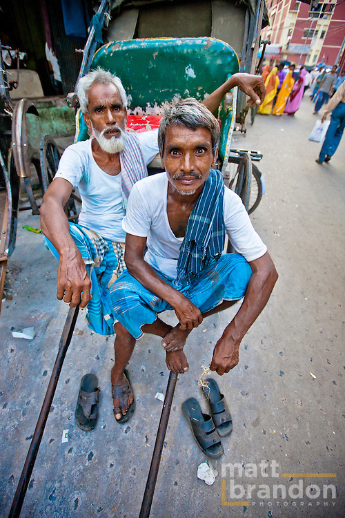 Two rickshaw pullers of Kolkata, India take a break using their rickshaw as a lounge chair.