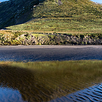 The mountainous landscape at Franklin Bay on Isla de los Estados, Argentina, is reflected in the shallow water on a beach at low tide.
