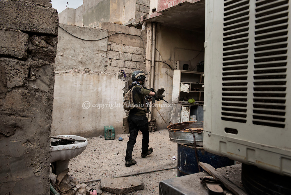 Iraq, Mosul: A he advances house by house a member of the Golden Division gestures to his comrades in west Mosul. Alessio Romenzi
