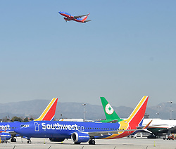 (Above)A Southwest jet 737 flies over a grounded 737 MAX 8 the last one at LAX  after the past 24 hours Thursday, international concern over the possible dangers of Boeing's 737 Max 8 aircraft has only continued to grow..US President Donald Trump announced Wednesday afternoon he would immediately ground all Boeing 737 Max 8 and 9 aircraft, amid concerns over their involvement in two major plane crashes less than six months apart...Boeing issued a statement saying they would recommend the temporary global suspension of the entire 737 Max fleet. Fifty countries have now grounded or banned the planes inside their airspace. March 14,2019..Photo by Gene Blevins/ZumaPress. (Credit Image: © Gene Blevins/ZUMA Wire)