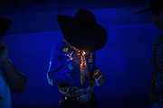 Bull rider and farmer Igor Torres, 18 lights a hand rolled cigarette before the start of a rodeo in Goiania, Brazil, Friday, Dec. 16, 2016. Considered one of the economic pillars of Brazil, hoarding increasingly huge swaths of land and spreading the same amounts of environmental degradation and land conflicts, the powerful agribusiness finds its heart, soul and voice in the city of Goiânia. Home of a million and a half souls it sits on the immense central plains of Brazil and nurtures a rodeo culture and cowboy lifestyle challenging its own urbanization, highlighting the archaic and rural character of Brazilian mindset and its society. (Dado Galdieri for the New York Times)