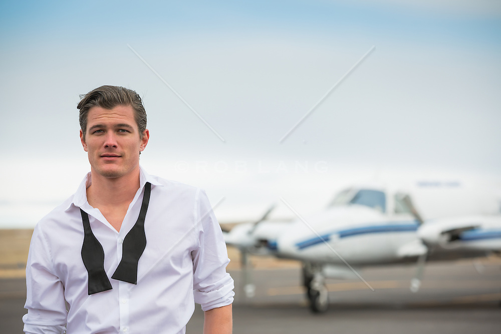 handsome man in a tuxedo shirt and loose tie at a private airport outdoors by a jet