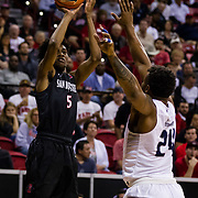 09 March 2018: San Diego State men's basketball takes on Nevada in the quarterfinal round of the Mountain West Conference Tournament. San Diego State Aztecs forward Jalen McDaniels (5) goes up for a jump shot with Nevada Wolf Pack guard Jordan Caroline (24) in his face in the first half. The Aztecs cruise past the Wolfpack 90-73 to move on to the Championship game tomorrow afternoon at 3pm.<br /> More game action at www.sdsuaztecphotos.com