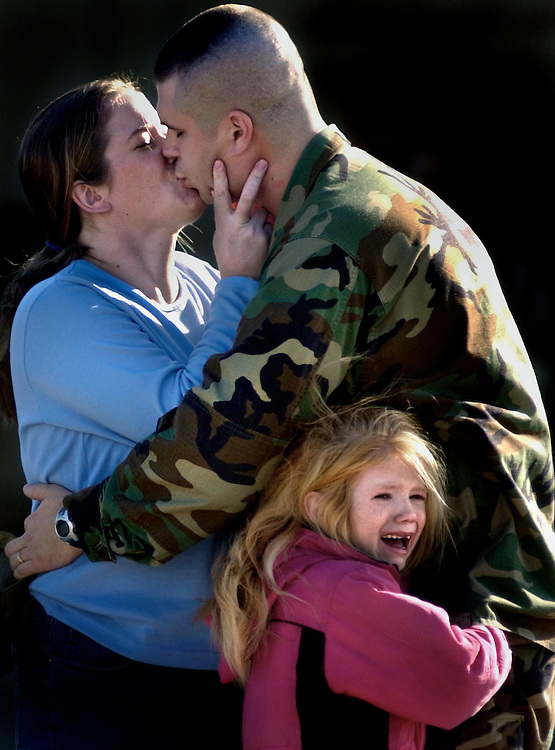 Amy Greer kisses her husband Staff Sgt. Anthony Greer as his daughter Ashley, 6, holds on to him before his deployment Tuesday from the MCAS in Beaufort South Carolina to the Persian Gulf.
