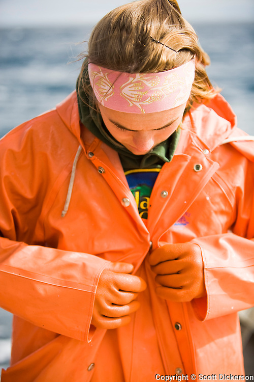 Claire Laukitis put on raingear while commercial sockeye salmon fishing in the Eastern Aleutian Islands, area M, region aboard the F/V Lucky Dove.