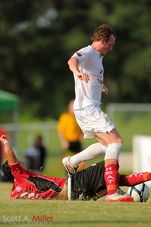 Orlando City midfielder Alexander McDonald (17) leaps over Laredo Heat midfielder Armando Begines (23) during the Orlando City U23s 2-1 win in their PDL Southern Conference Championships playoff game at Trinity Catholic High Schooll on July 20, 2012 in Ocala, Florida. ..©2012 Scott A. Miller
