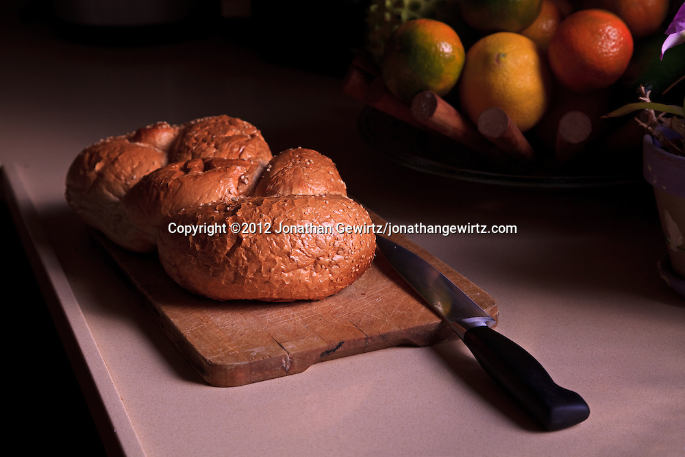 A loaf of challah bread on a cutting board with a bowl of fruit in the background. WATERMARKS WILL NOT APPEAR ON PRINTS OR LICENSED IMAGES.