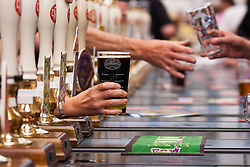 Olympia, London, August 12th 2014. Olympia, London, August 12th 2014. Brisk business is done at the pumps as hundreds of people sample 900 different real ales, international beers, ciders and perries at the CAMRA Great British Beer Festival.