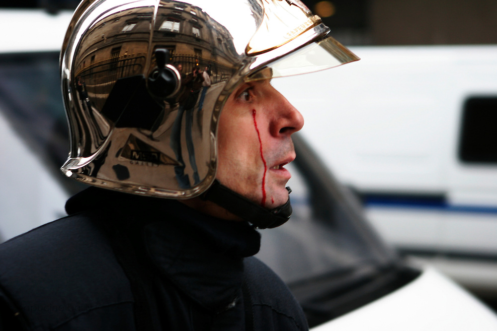 March 23rd 2006. Esplanade des Invalides, Paris, France..A fire fighter watches the violent clashes that erupted during a student protest against the First Job Contract, known as CPE. The country's main student union condemned the violence, which police blamed on fringe groups of radicals and anarchists.