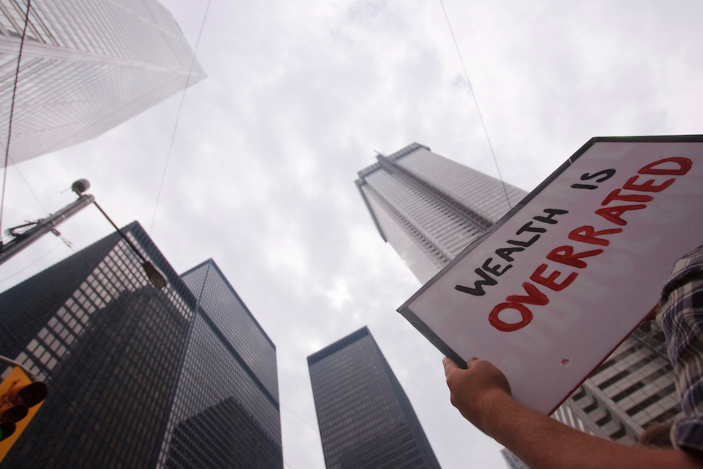 A Protestor holds a sign during a peaceful protest in the financial district of Toronto, Canada during the final day of the G20 summit June 27, 2010<br /> AFP/GEOFF ROBINS/STR