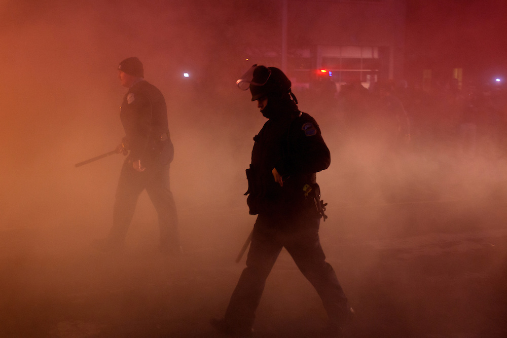 Police walk through a cloud of tear gas and smoke from a cruiser that had been set ablaze. Law enforcement worked around the clock to bring order back to the streets of Ferguson. Demonstrations turned violent after the grand jury failed to indict Officer Darren Wilson for the shooting death of Michael Brown Jr.