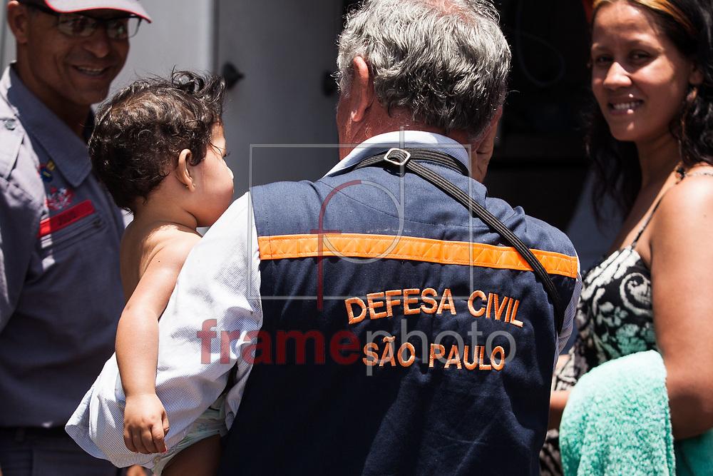São Paulo, SP - 22/01/2014 - O coordenador da Defesa Civil de São Paulo, coronel Jair Paca de Lima, ajuda a retirar moradores de incêndio que atingiu dois andares de um edifício residencial na esquina das ruas dos Protestantes e General Osório, no Centro de São Paulo, região da Luz, na manhã de hoje. Onze viaturas dos bombeiros e o helicóptero Águia da Polícia Militar foram deslocados para o local, mas não houve vítimas. Bombeiros e homens da Defesa Civil ajudaram a retirar moradores do local. Foto: Rodrigo Dionisio/Frame