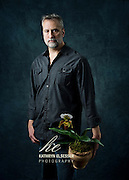 Business Portrait of Josef of Botanica Floral Design holding a potted orchid