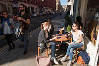 Two London-based German ladies enjoy a coffee at Monocle, a café created by Tyler Brûlé, who created the Monocle magazine créateur. Chiltern Street, Marylebone, London.