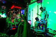 Tourist joins the go go dance in a gay bar in a busy street of Kuta, Bali, Indonesia. The gay bars have became a touristic attraction for people who curious about it.