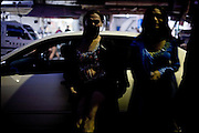 """Kate and Nadia (from the left),  30 and 21 years old, transvestites, leant on a big car rent from the bridegroom just for their performance at his wedding party. Early morning in Lahore, Pakistan on Wednesday, December 03 2008.....""""Not men nor women"""". Just Hijira, Kusra. Painted lips, Kajal surrounding their eyes and colourful veils..Pakistan is today considered a strongly, foundamentalist as well, islamic country. But under its reputation, above all over the talebans' continuos advancing, stirs a completely extraneous world, a multiethnic mixed society. Transvestites make part of it, despite this would not be admitted by a strict law. Third gender, the Hijira are born as men (often ermaphrodites) or with an ambiguous genital situation, and they have their testicles and penis removed through a - often brutal - surgical operation. The peculiarity is that this operation does not contemplate the reconstruction of a female organ. This is the reason why they are not considered as men nor women, just Hijira. They are often discriminated, persecuted  and taxed with being men prostitutes in the muslim areas. The members of this chast perform dances during celebrations, especially during weddings, since it is anciently believed that an EUNUCO's dance and kiss in the wedding day brings good luck to the couple's fertility...To protect the identities of the recorded subjects names and specific .places are fictionals."""