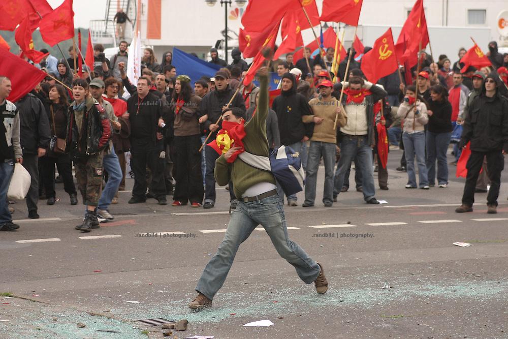 Ein Demonstrant wirft einen Stein gegen die Polizei. Mehrere zehntausend Globalisierungsgegner demonstrierten in Rostock gegen den nächste Woche stattfindenden G8-Gipfel in Heiligendamm. Noch vor dem Beginn der Abschlußkundgebung kam es zu schweren Auseinandersetzungen zwischen der Polizei und Dmeonstranten. Wasserwerfer und Tränengas wurden gegen Demonstranten eingesetzt. Ein Auto brannte und Seine flogen. Zahlreiche Menschen wurden dabei verletzt. Serveral tenthousands Anti-Globalisation protesters demonstrate in Rostock against the G8 Summit in Heiligendamm. During the Demsonstration heavy riots between protesters and policemen took place near the Rostock port. A car burned down and stones were thrown. Serveral people became injured.