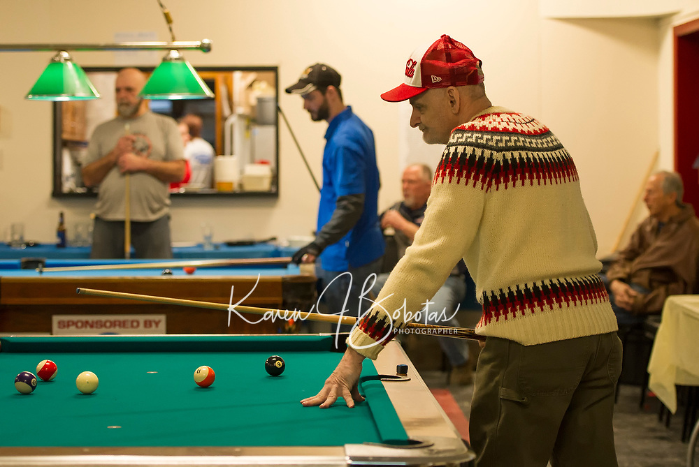 Jim O'Neil looks over the table before making his shot during the Robbie Mills 8-ball Tournament at the Laconia Rod and Gun on Saturday.  (Karen Bobotas/for the Laconia Daily Sun)