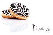 Zebra donuts with dark and white chocolate cream, over white background.