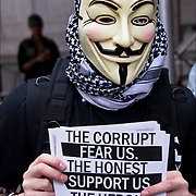 Close up of masked &quot;Anonymous&quot; protester, member holding an Anonymous flier at Occupy Wall Street, protest on September 17, 2011.<br /> <br /> Anonymous is a group initiating active civil disobedience and spread through the Internet while staying hidden, representing the concept of many online community users simultaneously existing as an anarchic, digitized global brain. <br /> <br /> It is also generally considered to be a blanket term for members of certain Internet subcultures, a way to refer to the actions of people in an environment where their actual identities are not known.