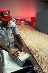 snack Food manufacturing industiral plant workers oversee pretzel assembly line