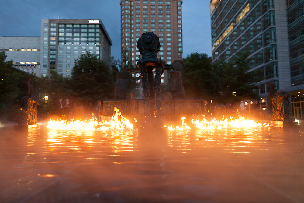 """La Joute (""""the joust"""") (1969) is a public sculptural installation by Quebec artist Jean-Paul Riopelle. The fountain operates on a kinetic sequence that takes about 32 minutes to complete.  On the hour, it shoots up jets of natural gas through the water; producing a dramatic ring of flame which lasts for about seven minutes. The mist sequence, without the fire in the fountain, occurs every hour throughout the day."""
