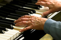 A close-up of a senior's hands depict the telltale signs of aging while playing on a piano in an old folks home.  Courtenay, The Comox Valley, Vancouver Island, British Columbia, Canada.