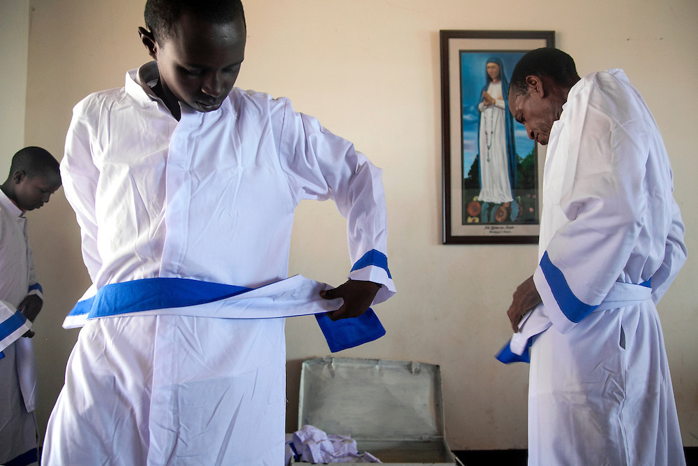 Choir members pull on their robes before mass at The Shrine of Our Lady of Sorrows in Kibeho, Rwanda.<br /> This is the only sanctioned Marian sanctuary in Africa. Kibeho's overseers and the Rwandan government hope this place will become a top tourism site. <br /> <br /> Photographed, Sunday, October 26, 2014.<br /> <br /> Photo by Laura Elizabeth Pohl