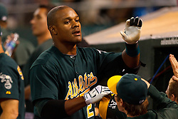 September 20, 2011; Oakland, CA, USA;  Oakland Athletics center fielder Michael Taylor (23) is congratulated by teammates in the dugout after hitting his first Major League home run against the Texas Rangers during the fifth inning at O.co Coliseum.