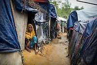 A woman, one of the 600,000 Rohingya who fled Myanmar in the two months since August 25, sits at the entrance to her shelter in Kutupalong refugee camp in Bangladesh. (October 29, 2017)