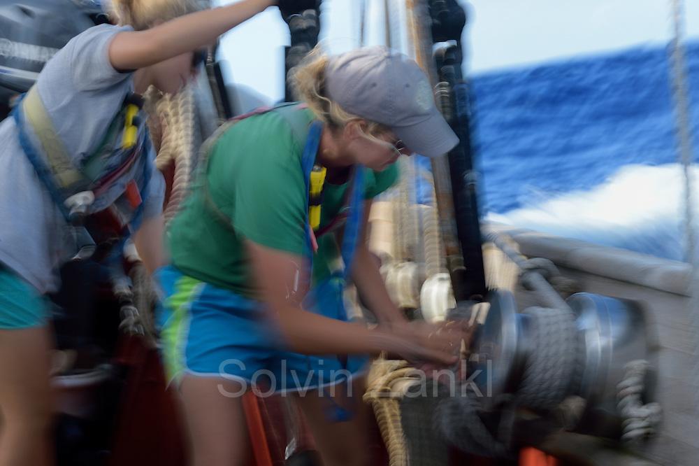 Corwith Cramer is a 134-foot steel brigantine built as a research vessel for operation under sail. Sargasso Sea, Bermuda | 2nd Mate Jill Hughes bedient die Winsch um die Vorsegel auf dem Forschungssegler Corwith Cramer zu trimmen. Der Forschungssegler Corwith Cramer durchquert im April 2014 die Sargasso See von Puerto Rico kommend bis zu den Bermuda Inseln.