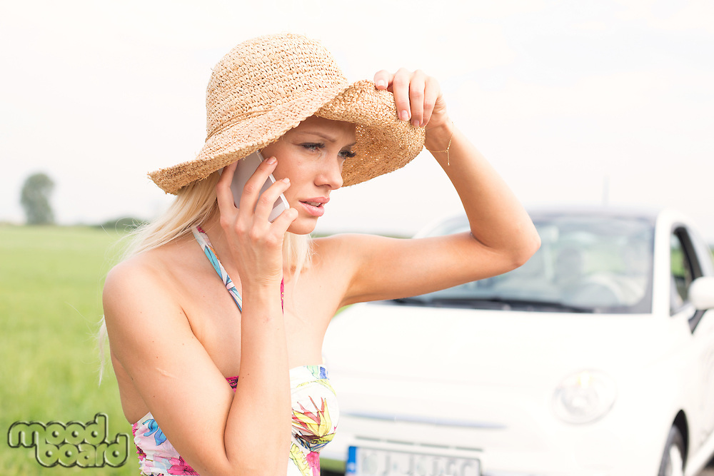 Frustrated woman using cell phone by broken down car
