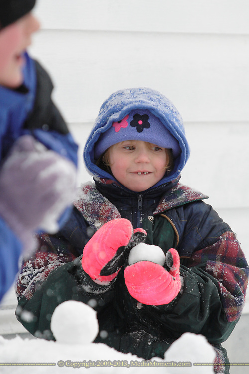 In Dayton's Belmont neighborhood, Destiny Richardson (right) 6, looks around with a snowball in hand, as Chance Textor, 10 prepares a snowball during Tuesday's Winter storm.