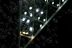 Bubbles float through the air in front of a floodlight at the London Stadium