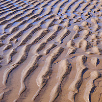 Tide and waves leave organic patterns in the sand.