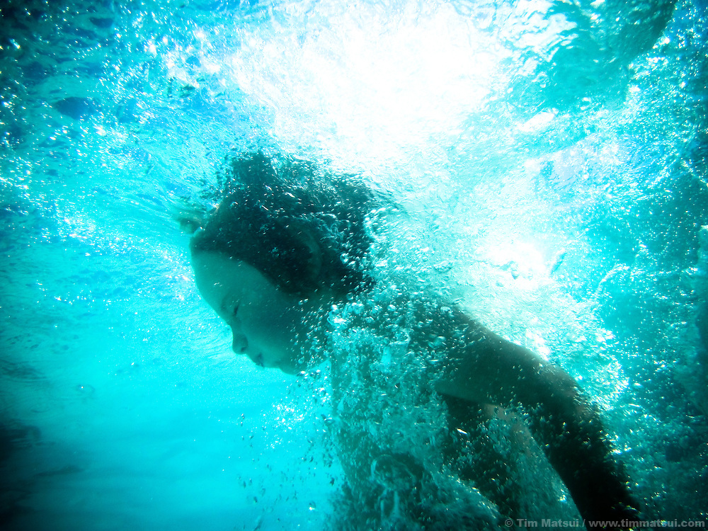 Young boy swims underwater.