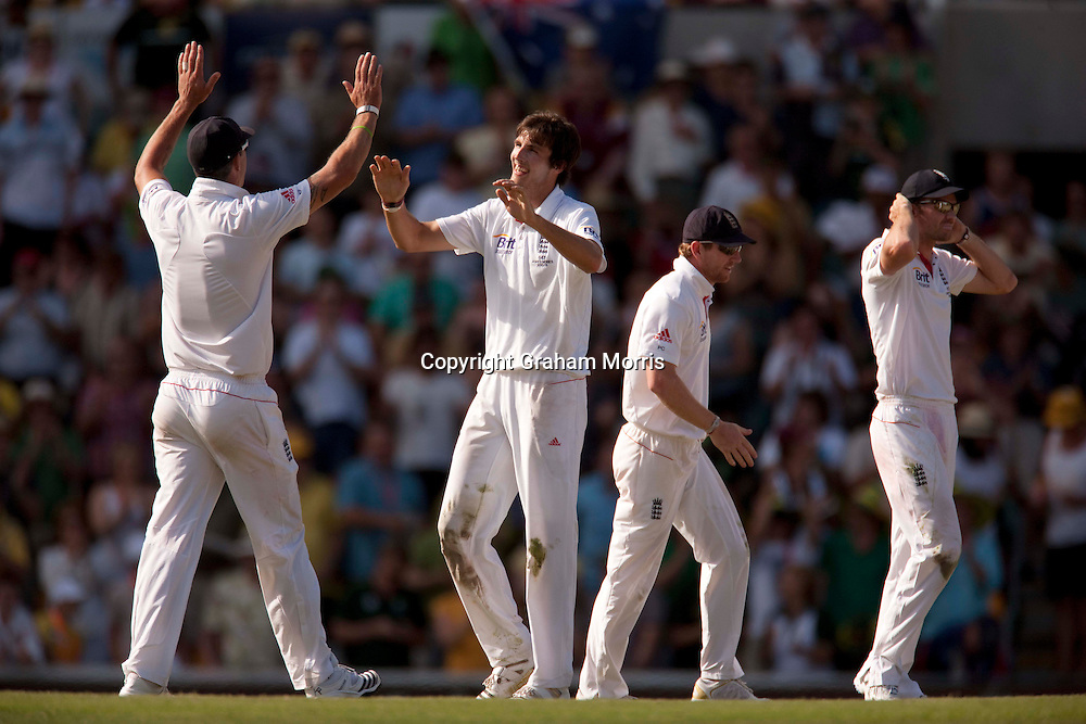 Steven Finn (bare-headed) celebrates taking the wicket of Michael Hussey (195) in the first Ashes Test Match between Australia and England at the Gabba, Brisbane. Photo: Graham Morris (Tel: +44(0)20 8969 4192 Email: sales@cricketpix.com) 27/11/10