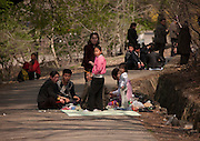 What can you do on sunday when you live in a dictatorship? You can hardly fly outside of the for a week end, or take your car to the beach...<br /> So this is the time to enjoy simple activities for the north koreans and the best opportunity for foreigners to meet them as everyone is more relax, including your minders!<br /> <br /> Photo shows:   For this family less wealthy, a small picnic will make their sunday. They were surprised to see a car coming as while were eating in the middle of the road in the suburb of Pyongyang.<br /> &copy;Eric Lafforgue/Exclusivepix Media