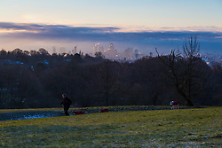 "A runner and his dogs on Hampstead Heath with The City's skyline in the background. The threatened snow from ""The Beast From The East"" weather system doesn't materialise overnight in London leaving a crisp, clear morning, seen from Hampstead Heath in North London. London, February 27 2018."