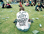 "View of the back of a young woman wearing a t-shirt with ""I Am A Very Naughty Girl"" written on it."
