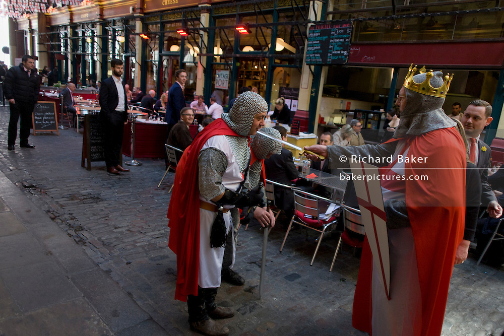 One St George knights another with mock sword in Leadenhall Market in the City of London, on England's national St George's Day the 23rd April,