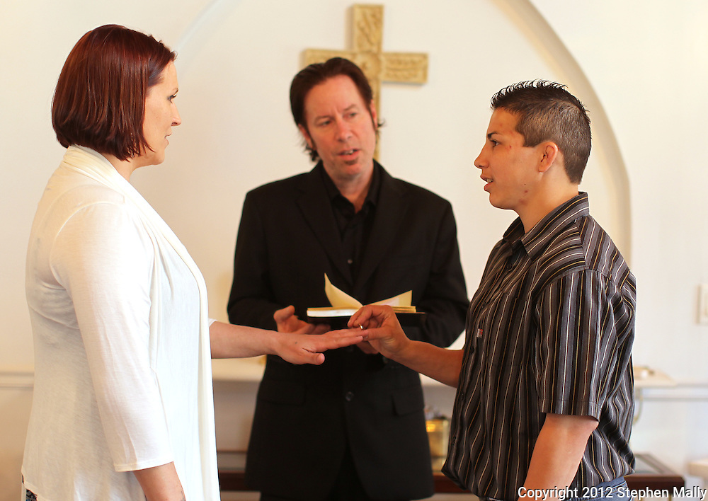 Stephany Lee (right) places a ring on the finger of Brigg McDonald (left) as Rev. Jonathan Harnish (center) looks on during their ceremony at a wedding chapel in Cedar Rapids on Monday, April 23, 2012.