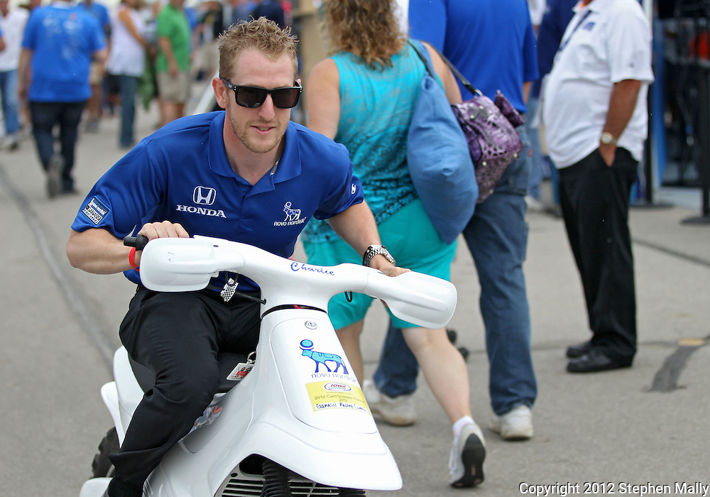 Charlie Kimball leaves an autograph session on a motorbike before the start of the IZOD IndyCar Iowa Corn Indy 250 auto race at the Iowa Speedway in Newton, Iowa on Saturday, June 23, 2012.