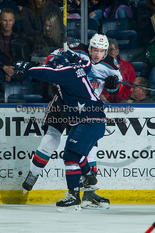 KELOWNA, BC - FEBRUARY 12: Connor Bouchard #19 of the Tri-City Americans checks Elias Carmichael #14 of the Kelowna Rockets into the boards during first period at Prospera Place on February 8, 2020 in Kelowna, Canada. (Photo by Marissa Baecker/Shoot the Breeze)