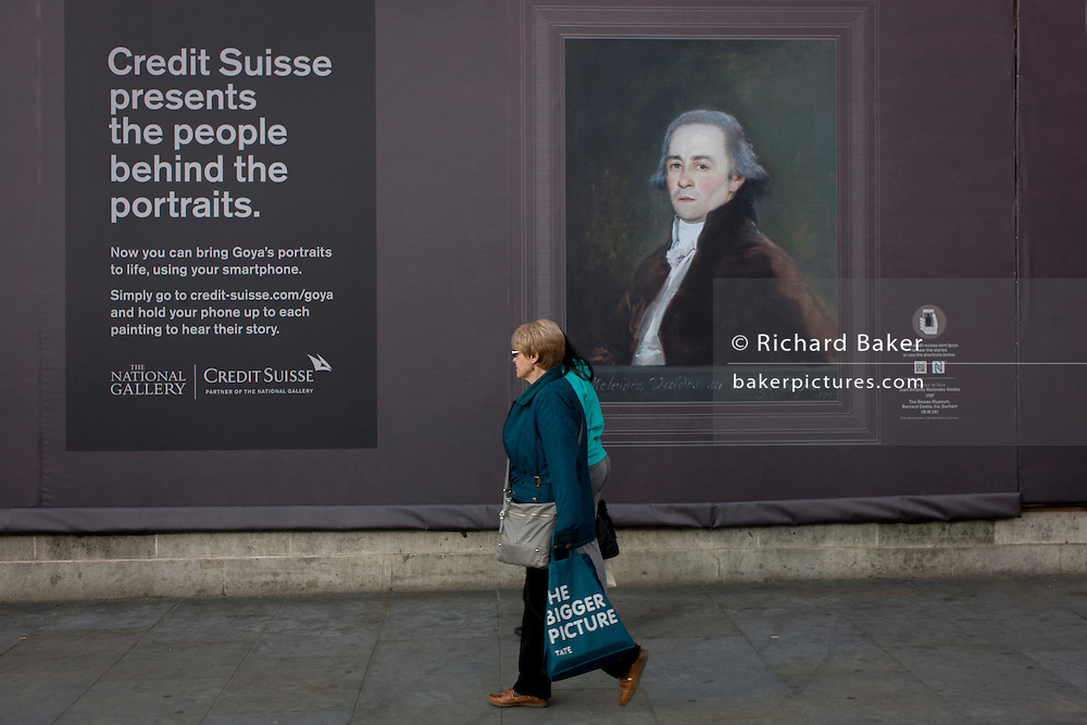 a woman walks with a Tate Modern gallery bag walks past a Goya portrait, sponsored by Credit Suisse and advertised on a construction hoarding outside the National Portrait Gallery.